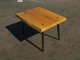 handmade wooden coffee table stands on the sand. craftwork photo