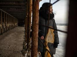 young girl in a coat stands near metal rusty structures near the sea photo