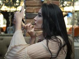 beautiful girl looks in a small mirror and paints her lips photo