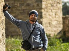 a bearded man stands against a wall in a fortress with a camera photo