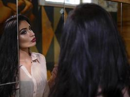 portrait of a beautiful girl with makeup looking into a large mirror photo