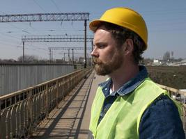 A man with a beard and mustache in a helmet stands on a bridge photo