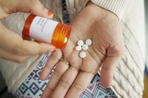 Cerca de la mano de la mujer tomando pastillas foto