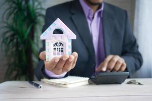 el concepto de concepto de finanzas, hombre con casa en mano foto