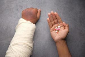 Mano dolorosa lesionada con vendaje y píldoras médicas en la mano foto