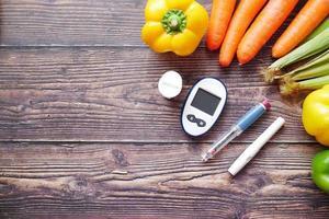 Herramientas de medición para diabéticos y verduras frescas en la mesa foto