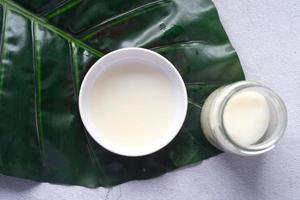aceite de coco en un recipiente y una hoja en la mesa foto