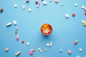 Vista superior de muchas píldoras y cápsulas de colores sobre fondo azul. foto