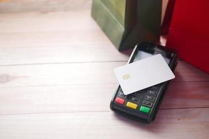 Payment terminal charging from a card, with shopping bag on table photo
