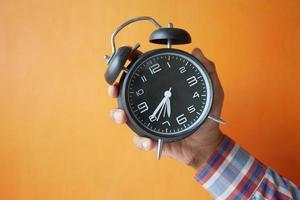 Persona mano sujetando el despertador contra el fondo naranja, foto