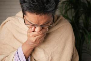 Mature man felling sick and coughs at home photo