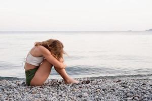 young depressed woman sitting on the beach looking away, rear view photo