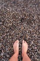 Bare female feet on pebble stones beach, top view photo
