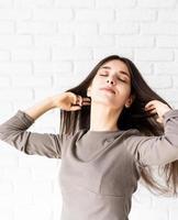 Mujer con cabello largo sobre fondo de pared de ladrillo blanco con los ojos cerrados foto