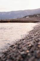 Playa de piedras de guijarros y el mar, fondo de naturaleza foto