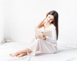 mujer en ropa blanca acogedora leyendo un libro foto