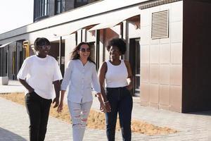 niñas felices de diferentes nacionalidades están caminando por la calle foto