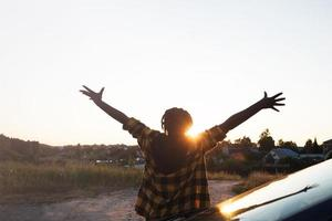 happy African-American woman near car looks at sunset, lifestyle photo