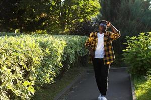 Feliz mujer afroamericana camina por la calle en el verano foto