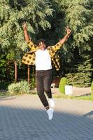 a happy African American woman in the park makes a jump in the summer photo