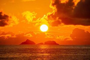 Sunset over Ipanema in Rio de Janeiro with orange sky and clouds photo