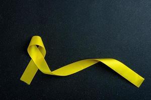 cinta amarilla sobre fondo de color. concepto de cáncer. foto