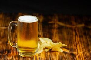 A glass of beer is placed on the wooden floor. photo