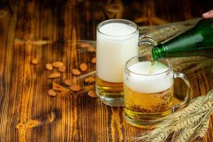 Glasses of beer placed on the wooden table photo