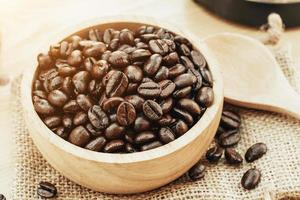 Coffee bean on wooden bowl with home made coffee background photo