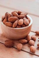 Almonds in wood bowl on wooden table background photo
