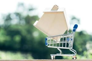 Miniature with mock up wood house on shopping cart photo