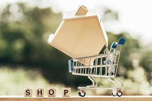 Miniatura con simulacro de casa de madera en carrito de compras y block word shop foto