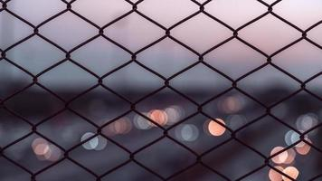 Chain link fence with light bokeh at sunset background photo