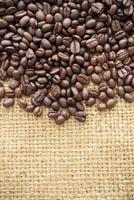 granos de café sobre fondo de arpillera foto