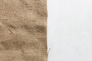 Textura de la vieja arpillera y mesa de madera blanca. foto