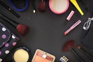 cosméticos de maquillaje y pinceles sobre fondo negro foto