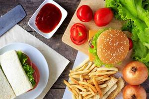 Grilled beef hamburger with vegetables on wood table photo