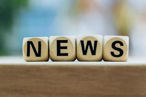 NEWS concept with wooden block on wooden table background photo