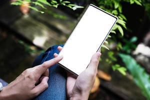 mano de mujer sosteniendo teléfono inteligente con pantalla en blanco foto
