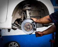Hombre mecánico reparación de frenos de disco de freno rueda de coches foto