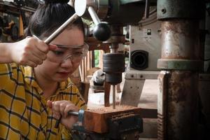 las mujeres de pie es artesanía trabajando madera de taladro foto