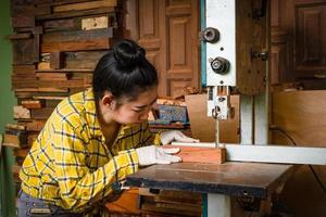 Las mujeres de pie es madera cortada de trabajo artesanal en un banco de trabajo foto
