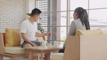 Happy Asian beautiful lifestyle family couple husband and wife laughing sitting in a cafe drinking coffee having talking conversation together inmorning. Two people in cafe enjoying. Slow motion video