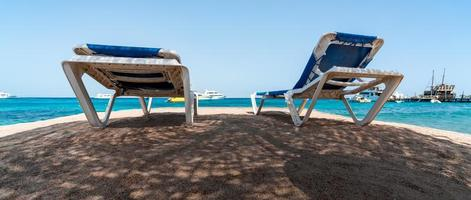 two beach loungers in the shade on the shores of the Red Sea photo