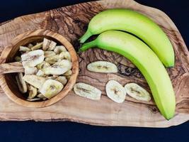chips de plátano secos sobre madera de olivo foto