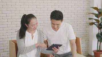 Asian family couple husband and wife work and using digital tablet. Cheerful loving couple smile shopping something online and watching social media together from home in living room, slow motion video