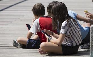 Children hooked to electronic devices in Madrid Rio Park, Madrid Spain photo