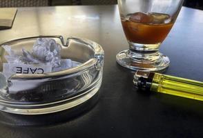café con hielo, mechero y cenicero foto