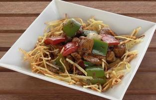 Pork tenderloin dish with French fries and green pepper photo