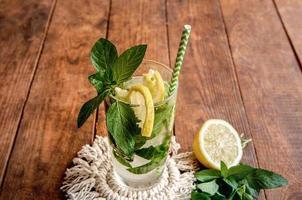 Limonada fría con limón sobre una mesa de madera marrón foto